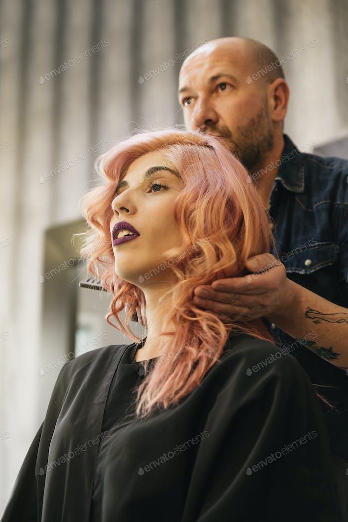 Schöne Frau bekommt Haarschnitt von Friseur.