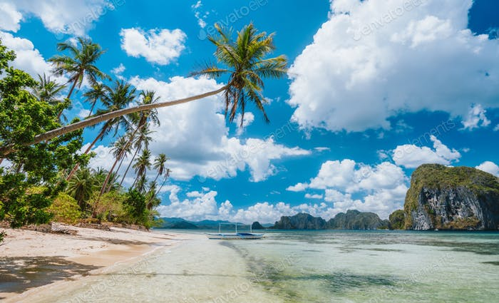 El Nido, Palawan, Philippines. Exotic beach with palm trees, tourist boat on the sandy beach and