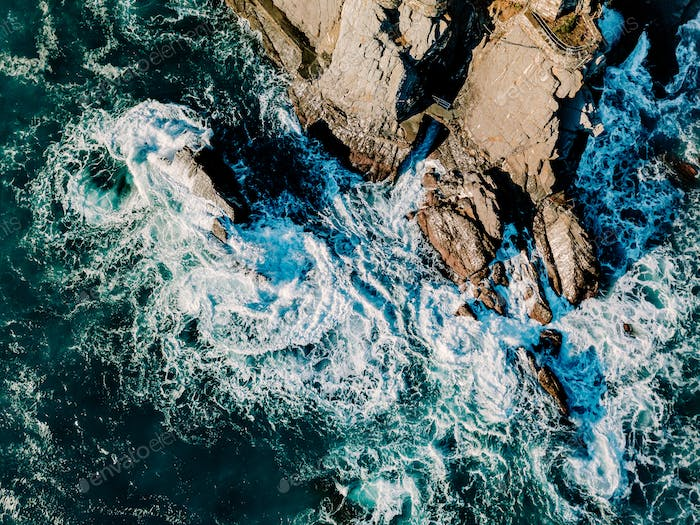 Aerial view of ocean waves and rocks. Blue  sea surface.