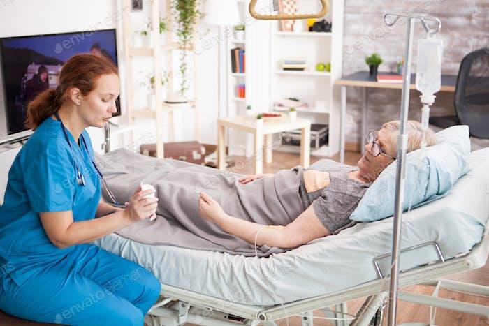Weibliche Krankenschwester im Gespräch mit älteren Mann über ihre Pillen