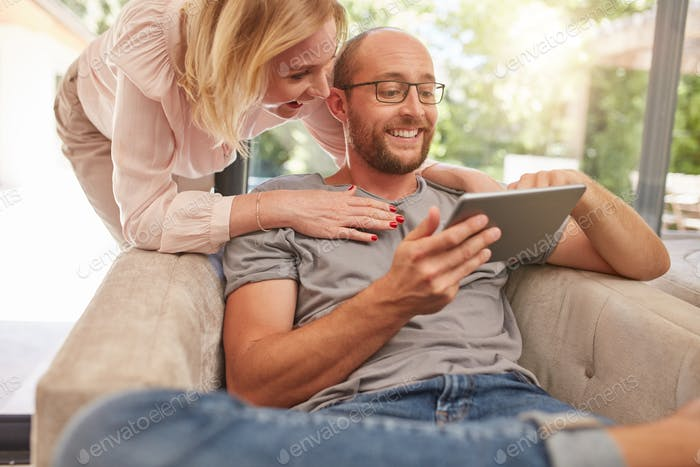 Couple using a digital tablet smiling