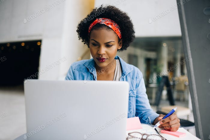 Focused young African female entrepreneur working on a laptop