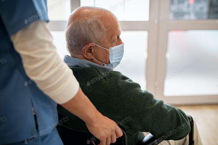 Старший мужчина в инвалидной коляске в доме преста