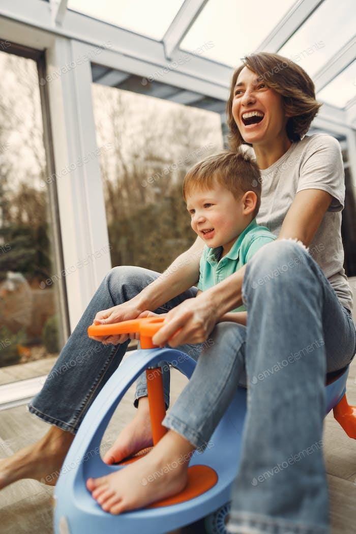 Mutter und Sohn gehen rund um die Wohnung auf einem Spielzeugauto