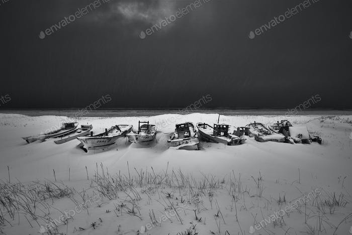 Fishing boats lying on dry land covered in snow and ice in winter.