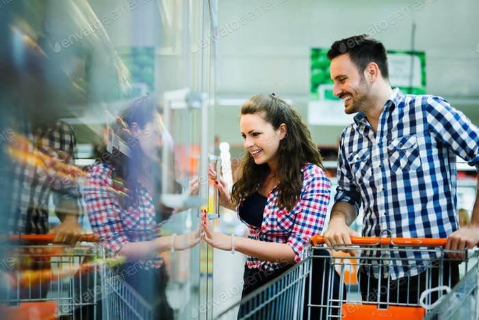 Couple shopping in supermarket while carrying shopping cart