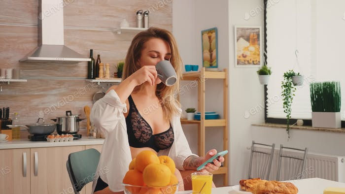 Seductive housewife in black lingerie using smartphone