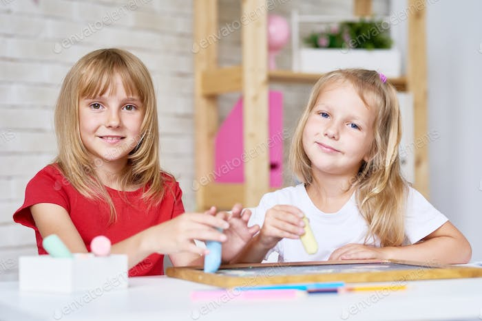 Cute Sisters Playing with Chalkboard