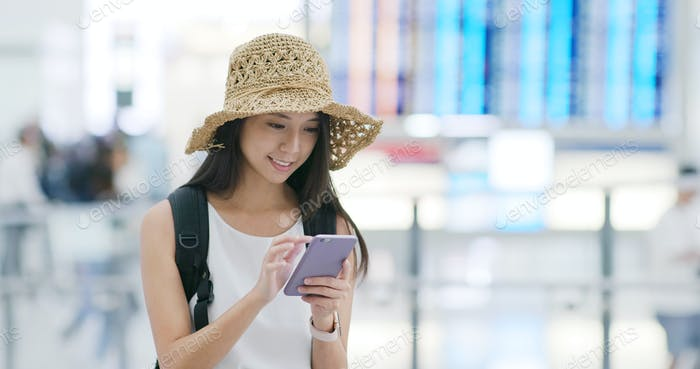 Woman check the flight number on cellphone in the airport