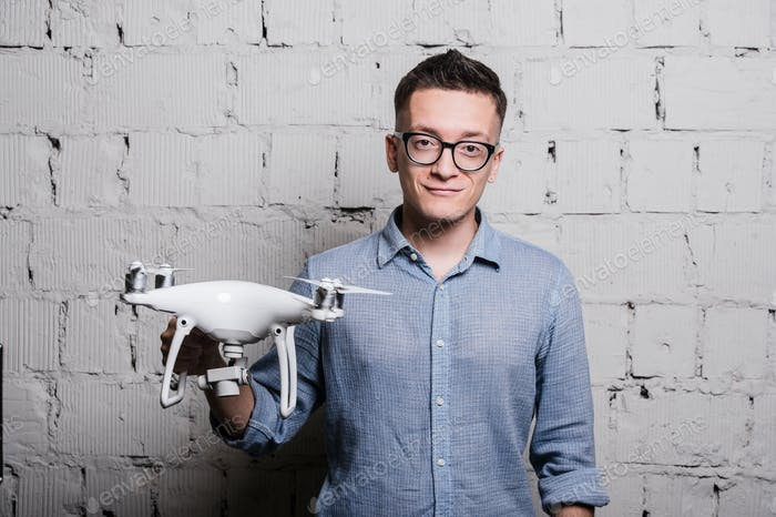 Young stylish Man in glasses with quadcopter drone on a grey brick wall