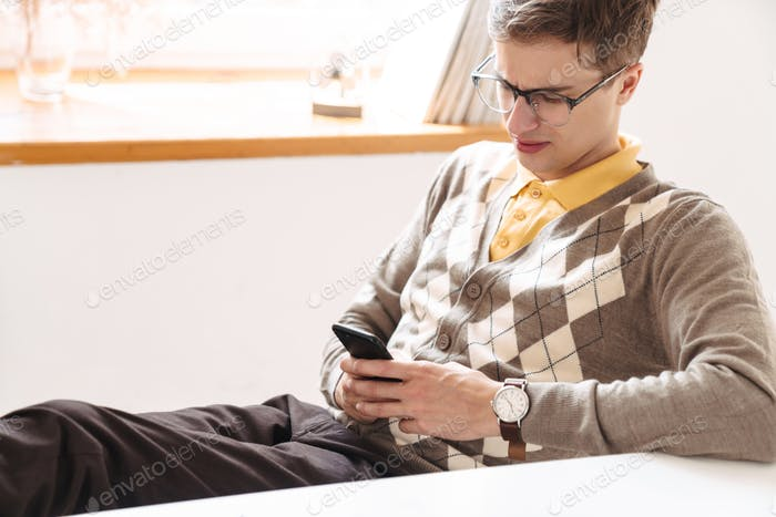 Guy student sit at the table indoors using mobile phone.