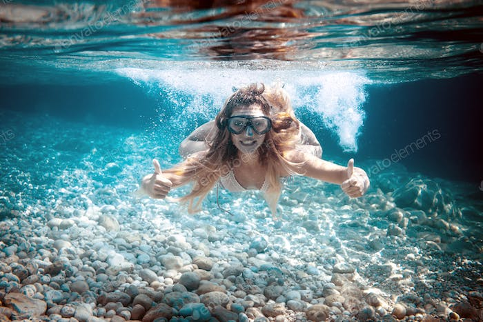 Snorkeling in the tropical sea, woman shows thumb up sign underwater