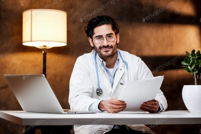 Positive doc sitting at the table in room with dark background