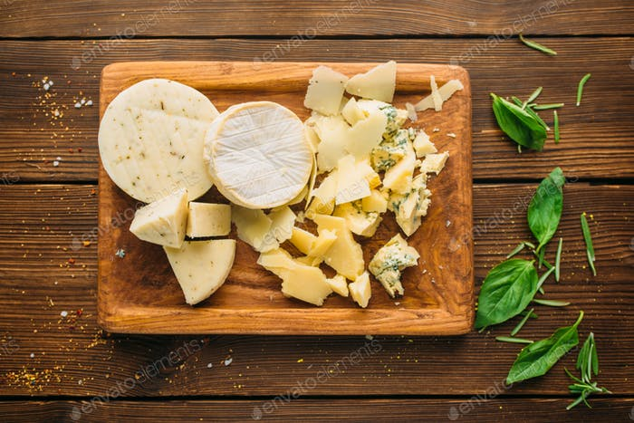 Cheese and herb on wooden table closeup, nobody