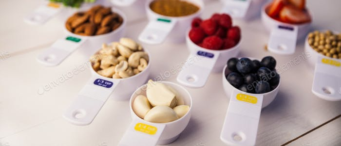 Portion cups of healthy ingredients on wooden table