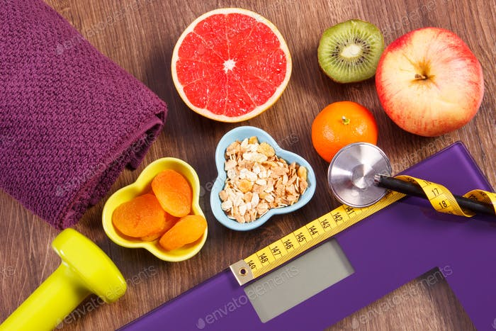 Electronic bathroom scale, centimeter and stethoscope, healthy food, dumbbells for fitness