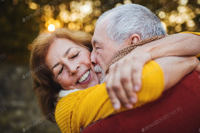 A senior couple standing in an autumn nature at sunset, hugging and kissing.