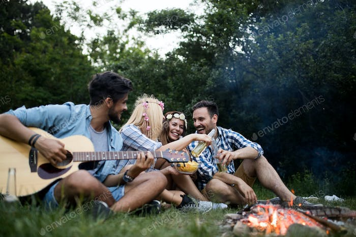 Friends playing music and enjoying bonfire in nature