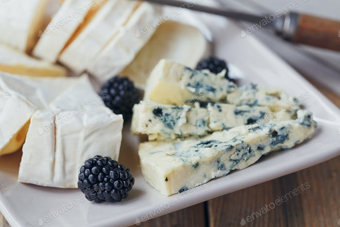Cheese plate. Assortment of cheese with berries