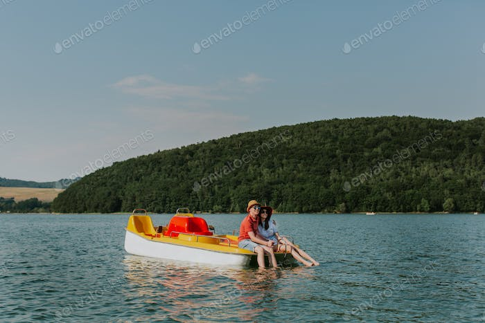 Couple in love resting on pedal boat with feet in water.