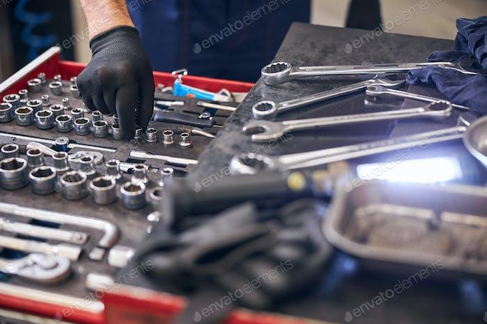 Auto mechanic taking socket from vehicle tools box