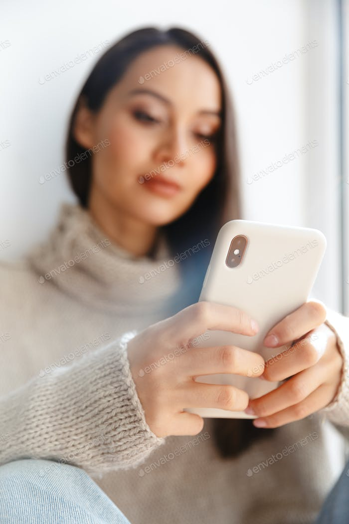 Image of asian woman typing on mobile phone while sitting on window sill