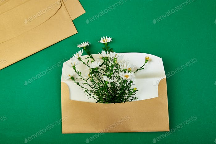 Goldfarbener Umschlag mit Frühlingsblumenarrangement