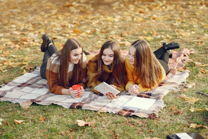 Girls sitting on a blanket in a autumn park