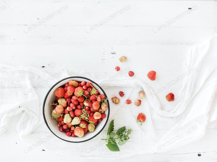 Wild strawberries in rustic metal bowl on white wooden background