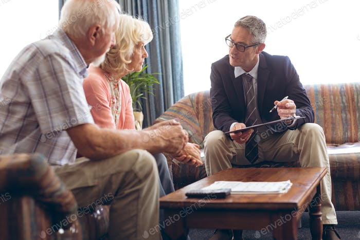 Male physician interacting with senior Caucasian couple at retirement home