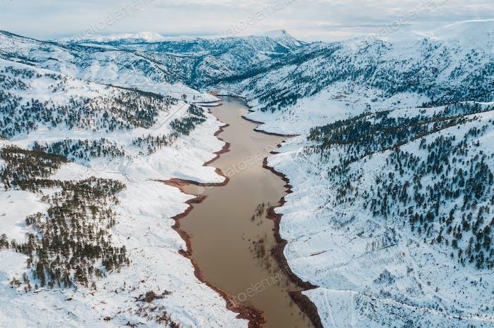 Luftaufnahme des Wintersees in verschneiten Bergen