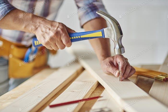 Carpintero con martillo golpeando clavos