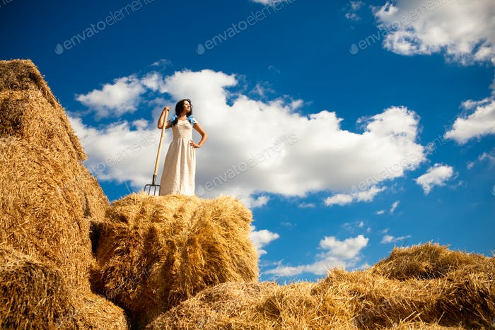 Young woman in white dress standing with hay pitchfork in hand in field