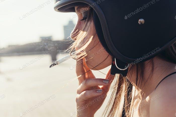 Schöne Frau im Motorradhelm Rauchen Sigarette