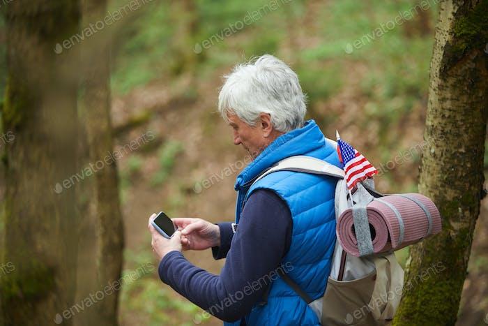 Senior Man Using GPS App in Forest