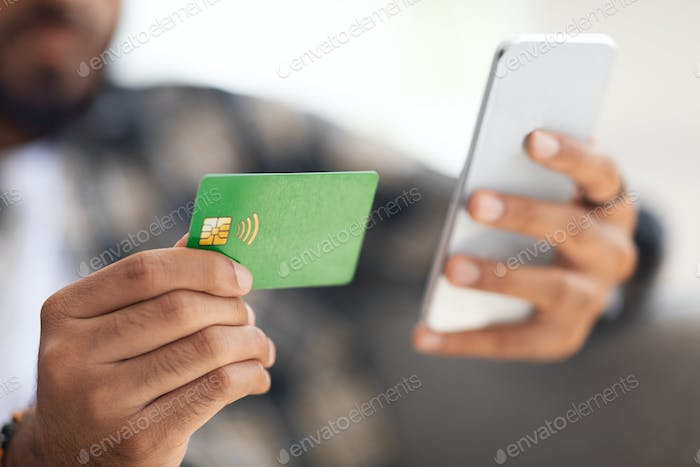 Credit card and modern mobile phone in male hands