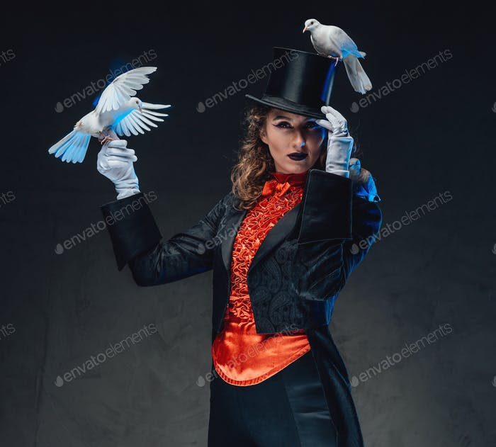 Eccentric woman with doves posing in dark background