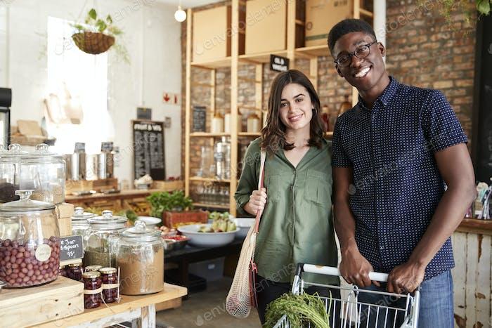 Porträt von paar mit trolley kaufen frisches obst und gemüse in kunststoff frei lebensmittelgeschäft