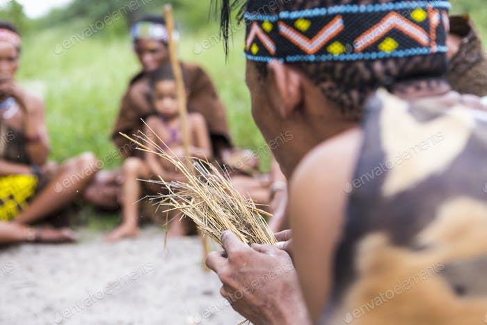 San People, a bushman creating fire from dry kindling, a cultural demonstration.