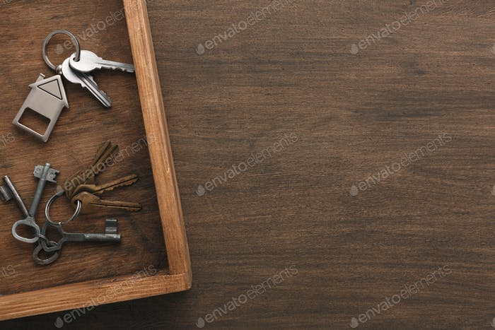 Many different keys on wooden tray