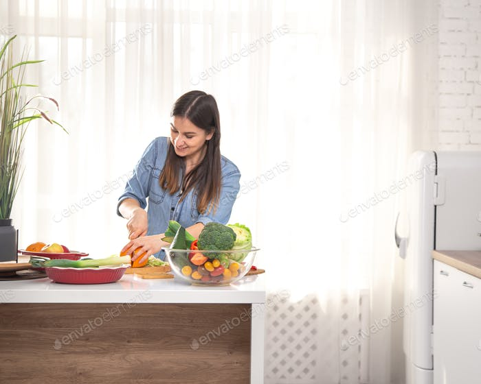 Young beautiful woman in the kitchen with fruits and vegetables.