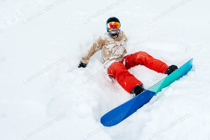 snowboarder is sitting in the snow with snowboard