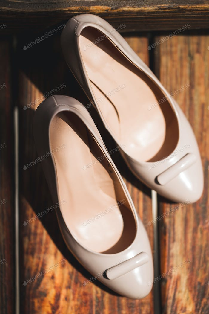 Classic beige fashion women shoes on high heels close-up on wooden texture