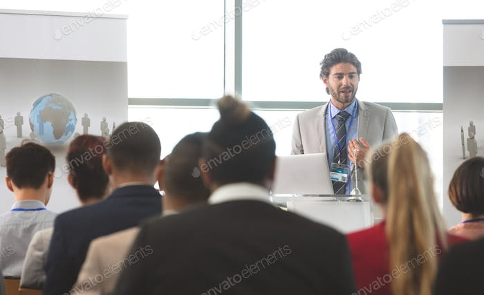 Businessman speaking in front of diverse group of business executives at business seminar in office