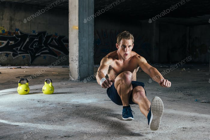Strong man squatting in abandoned building