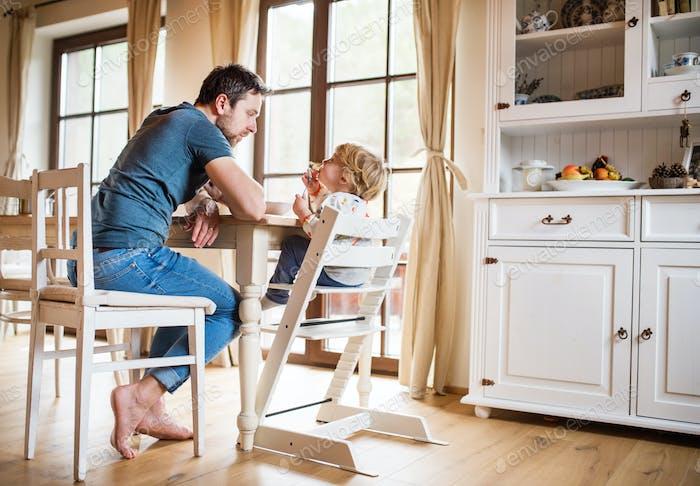 Padre sentado en la mesa con un niño pequeño en Página de inicio.