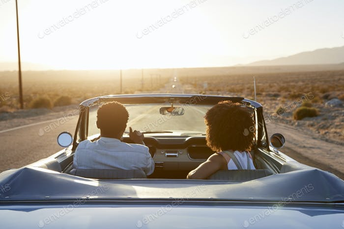 Rear View Of Couple On Road Trip Driving Classic Convertible Car Towards Sunset