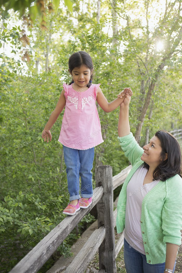 A young girl in a pink shirt and jeans, walking along a fence holding her mother's hand.