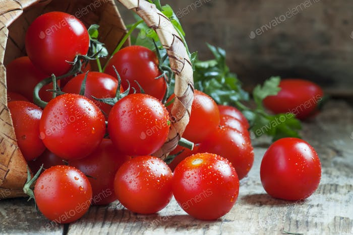 Small red cherry tomatoes spill out of a wicker basket