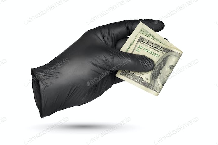 Hand holding hundred dollar bill in black protective glove isolated